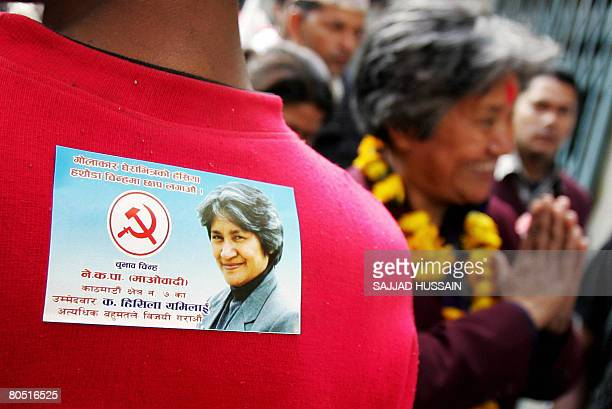 An activist of the Communist Party of Nepal has a poster of Nepal's minister for physical planning and construction Hishila Yami of the Communist...