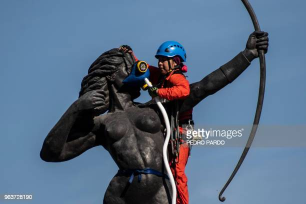 An activist of the environmental organization Greenpeace installs an oxygen tank and mask on the La Diana Cazadora monument to protest poor air...