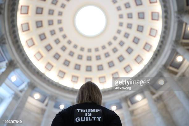 """An activist of the group Remove Trump participates in a """"Swarm the Senate"""" protest at the Rotunda of Senate Russell Office Building January 13, 2020..."""