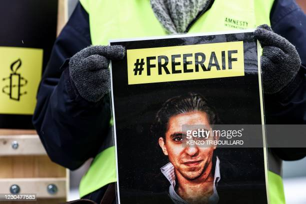 An activist of the human rights NGO Amnesty International holds a portrait of Raif Badawi in front of the embassy of Saudi Arabia in Brussels on...