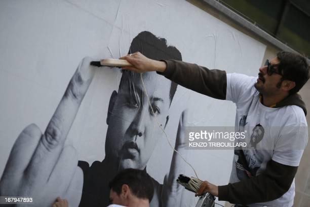 An activist of the international nongovernmental organization 'Reporters sans frontieres' sets on a wall a poster bearing a picture of North Korea...