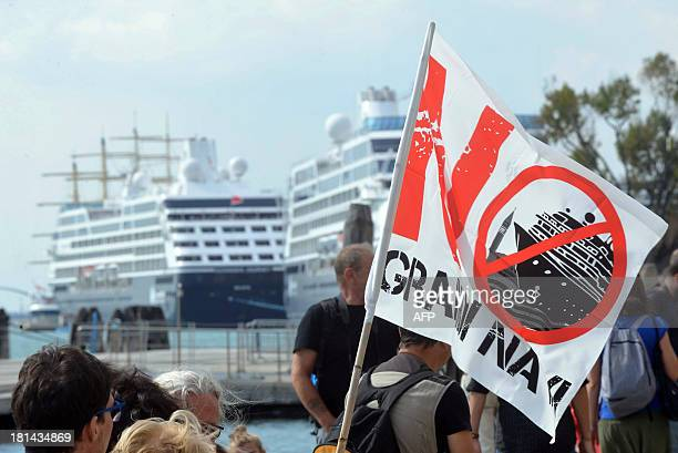 """An activist of the """"No Big Ships"""" movement holds a sign near the Venice lagoon during a protest against the presence of large cruise ships in the..."""