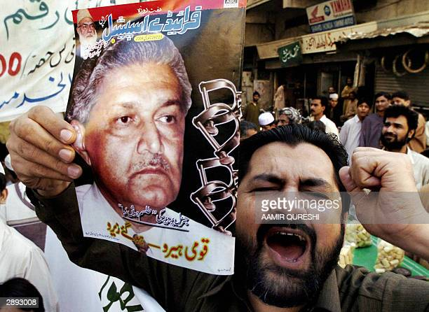 An activist of the rightwing JamateIslami displays a portrait of Pakistani nuclear scientist Abdul Qadeer Khan while shouting antigovernment slogans...