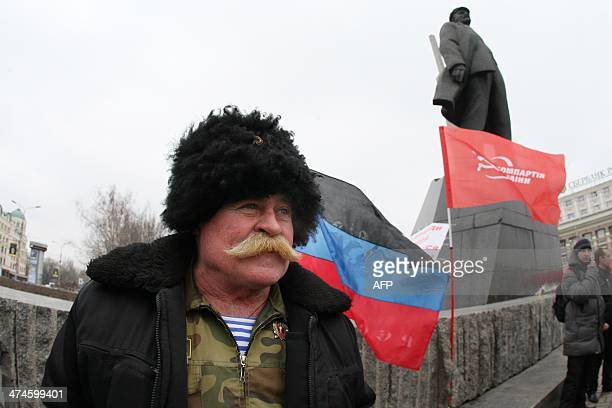 An activist of the Ukrainian Communist party together with a few others stands at the Lenin monument in the center of the industrial city of Donetsk...