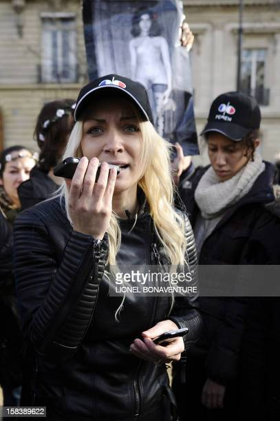 An activist of the Ukrainian women movement Femen speaks on the phone with Egyptian Aliaa Magda Elmahdy near the Egyptian embassy in Paris on...