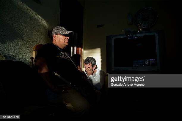 An activist of the Victims Mortgage Platform R rubs his face in next to Jorge Aviles at sunrise in his living room prior to start Jorge Aviles third...