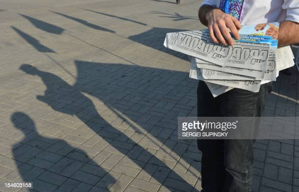 An activist of Ukrainian Svoboda party distributes newspapers and leaflets in the industrial city of Donetsk on October 23 2012 ahead of October 28...