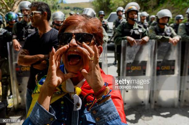 An activist opposing Venezuelan President Nicolas Maduro shouts slogans as security forces block their access to the funeral of Jose Diaz Pimentel...