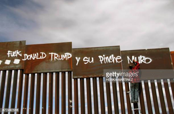 An activist paints the wall between the United States and Mexico during a demonstration against US President Donald Trump on the border of Ciudad...