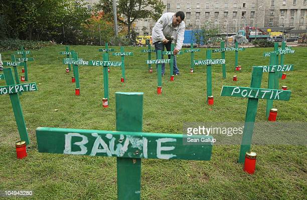 An activist pounds wooden crosses into the ground one for each of the 25 trees recently removed from Schlossgarten park next to Hauptbahnhof train...