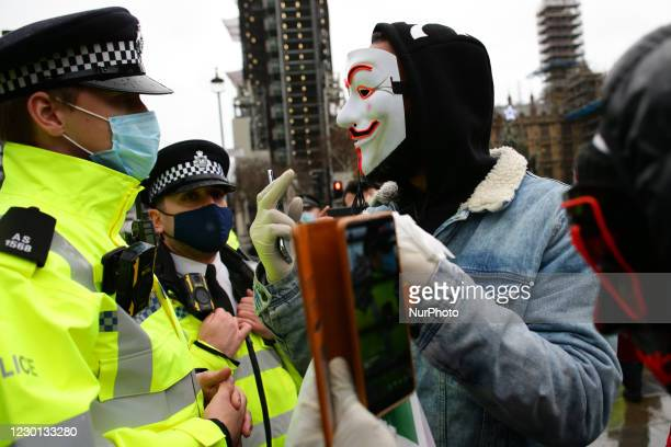 An activist protesting against coronavirus lockdown restrictions and any mandated covid-19 vaccinations wears a 'Guy Fawkes' mask while arguing with...