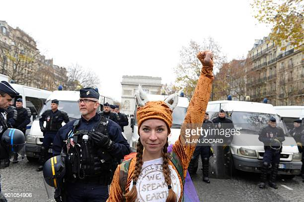 An activist raises her fist in front of French policemen as other activists gather to form a giant red line during a demonstration near the Arc de...