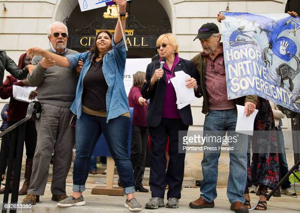 An activist representing the Penobscot Indians is third from left is held as she interrupts Attorney General Janet Mills at an anti Trump rally...