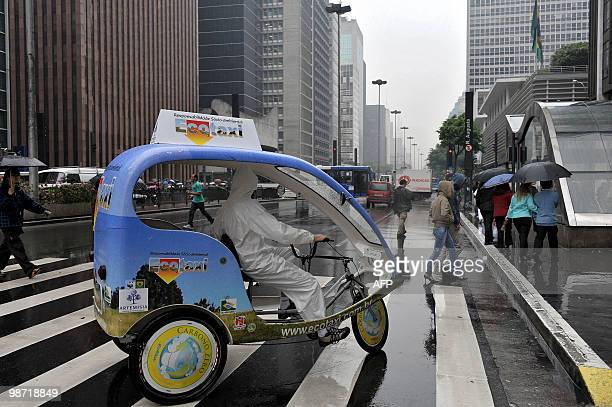 An activist rides a prototype taxi called 'EcoTaxi' a covered threewheel bicycle free of all carbon emissions through the financial district of...