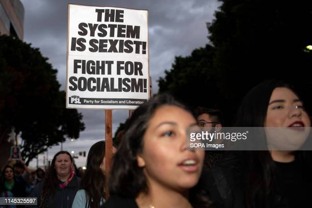 An activist seen holding a placard saying the system is sexist, fight for socialism during the International Women's Strike in Los Angeles. The rally...