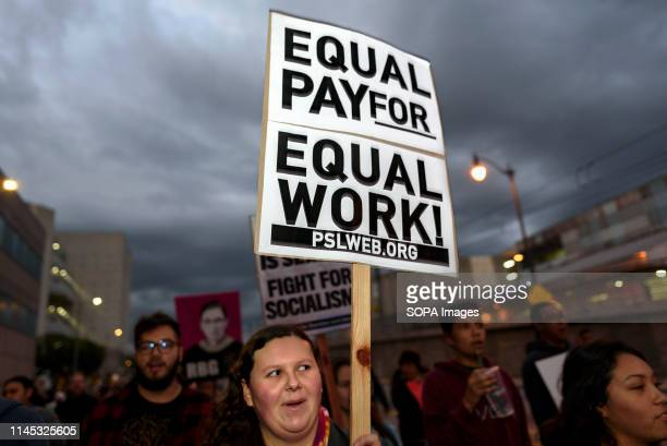 An activist seen holding a placard that says equal pay for equal work during the International Women's Strike in Los Angeles The rally coincided with...
