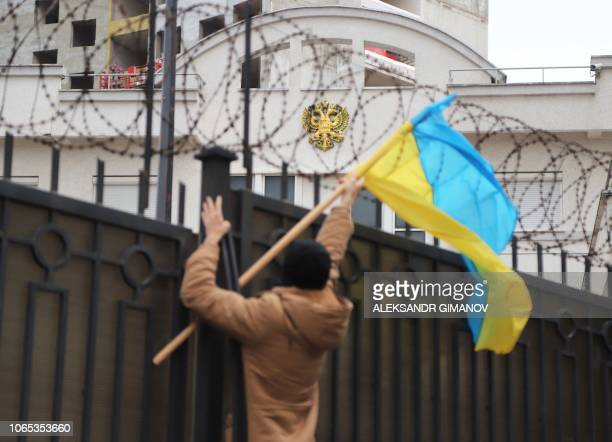 An activist sets a Ukrainian flag to the fence of Russian consulate during a protest action in Black Sea Ukrainian city of Odessa on November 26 2018...