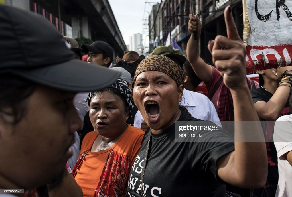 TOPSHOT - An activist shouts anti-Duterte slogans during a protest in Manila on November 30, 2017, denouncing the government's crackdown of activists and what they call US-backed Duterte dictartorship. Thousands of supporters and critics of Philippine President Rodrigo Duterte staged rallies on November 30 for and against his threat to declare a 'revolutionary government', which has fuelled fears of a looming dictatorship. /