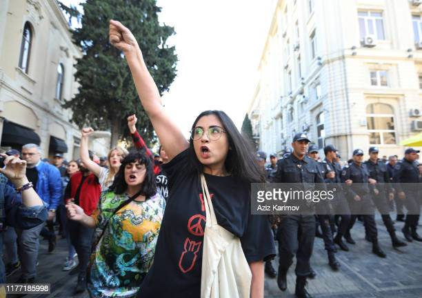 An activist shouts in front of police officers during a protest against domestic violence and violence against women in Baku on October 20 2019 in...
