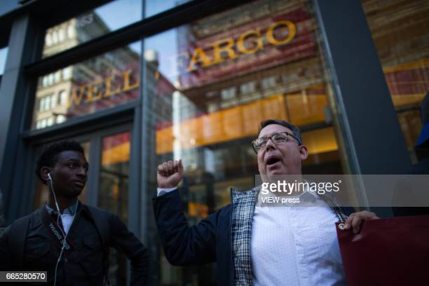 An activist shouts slogans agains wells Fargo as they begin the overnight camp out in front of Wells Fargo branch on April 5 2017 in Soho New York...