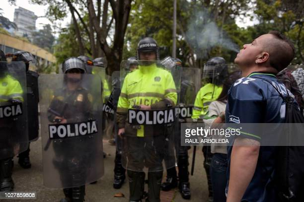 An activist smokes a joint defying police officers during a protest against the prohibition of bearing a minimum dose of marijuana for personal use...