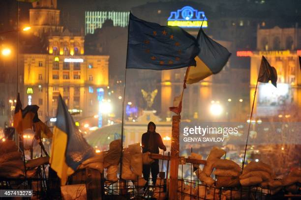 An activist stands atop a barricade flanked by the European Union and Ukrainian flags during an opposition rally on Independence Square in central...