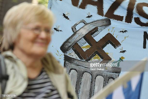 An activist stands in front of a banner showing a swastika being dumped into a garbage can during a demonstration to celebrate a court order banning...