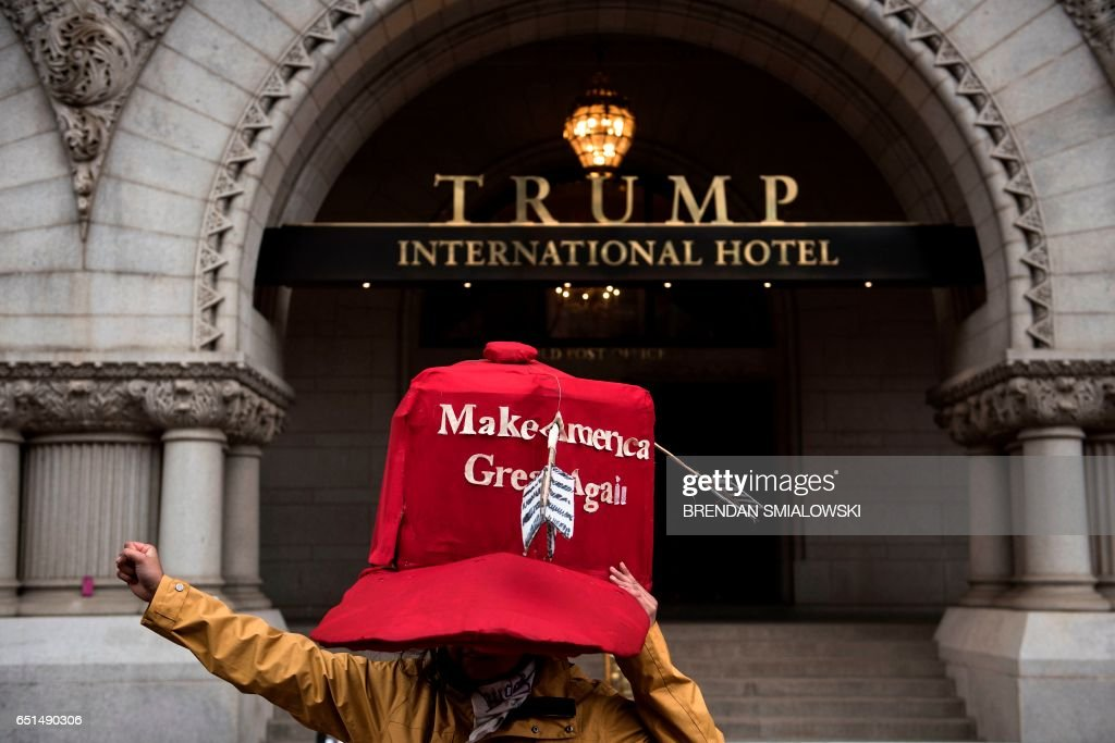 TOPSHOT - An activist stands in front of Trump International hotel while protesting the Keystone XL Pipeline and rallying for Native American rights march during the Native Nations Rise protest March 10, 2017, in Washington, DC. Native tribes from around the US gathered for four days of protest against the administration of US President Donald Trump and the Dakota Access oil pipeline. / AFP PHOTO / Brendan Smialowski