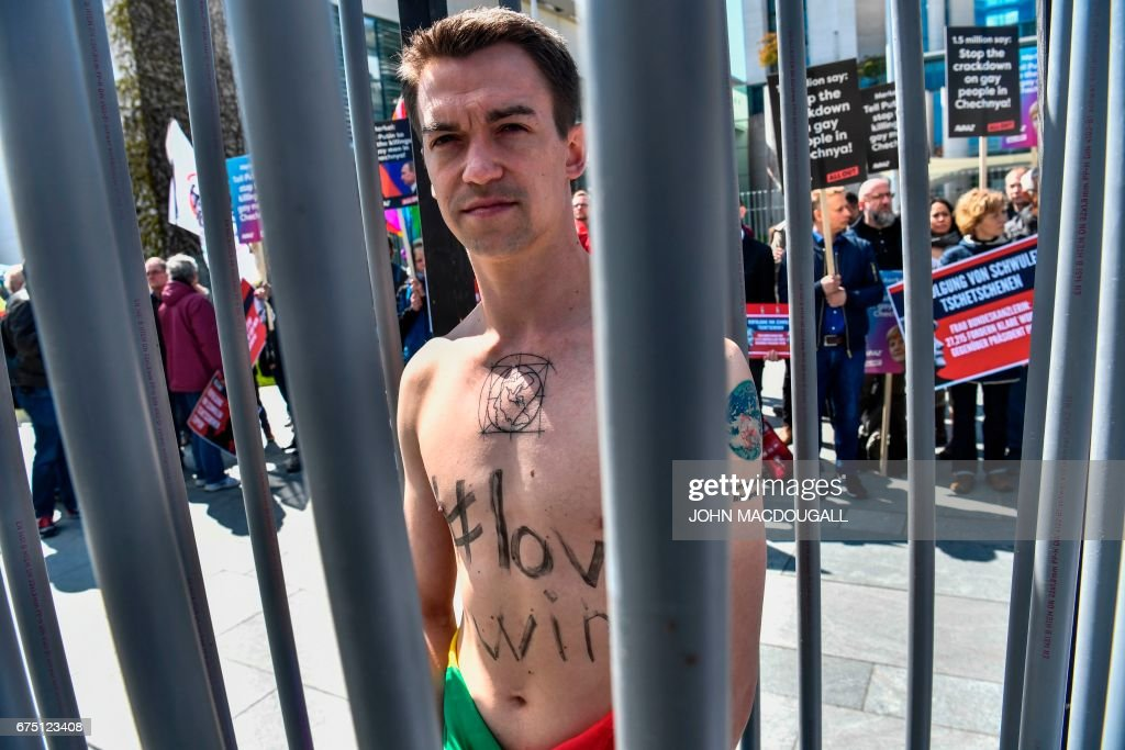 An activist stands naked, wrapped in a rainbow flag, in a mock cage in front of the Chancellery in Berlin on April 30, 2017, during a demonstration calling on Russian President to put an end to the persecution of gay men in Chechnya. The protestors called on German Chancellor Angela Merkel, who will meet Putin in Sochi on May 2, 2017, to raise the issue with him. / AFP PHOTO / John MACDOUGALL