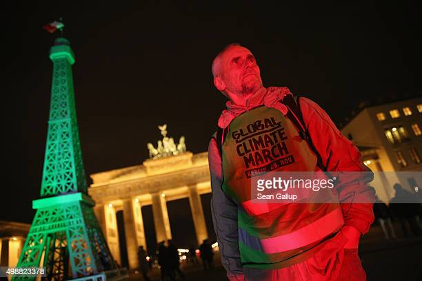 An activist stands next to an effigy of the Eiffel Tower bathed in green light in front of the Brandenburg Gate ahead of climate change marches...