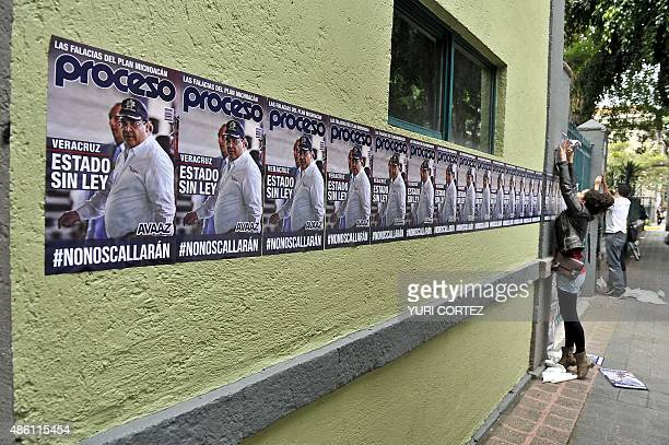 An activist sticks posters with the image of Veracruz state governor Javier Duarte reading State without law outside the representative office of the...