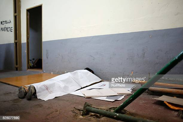 An activist tries to sleep with the only protection against the cold of a poster which uses as a blanket in the garage of the number 29 Street Ofelia...