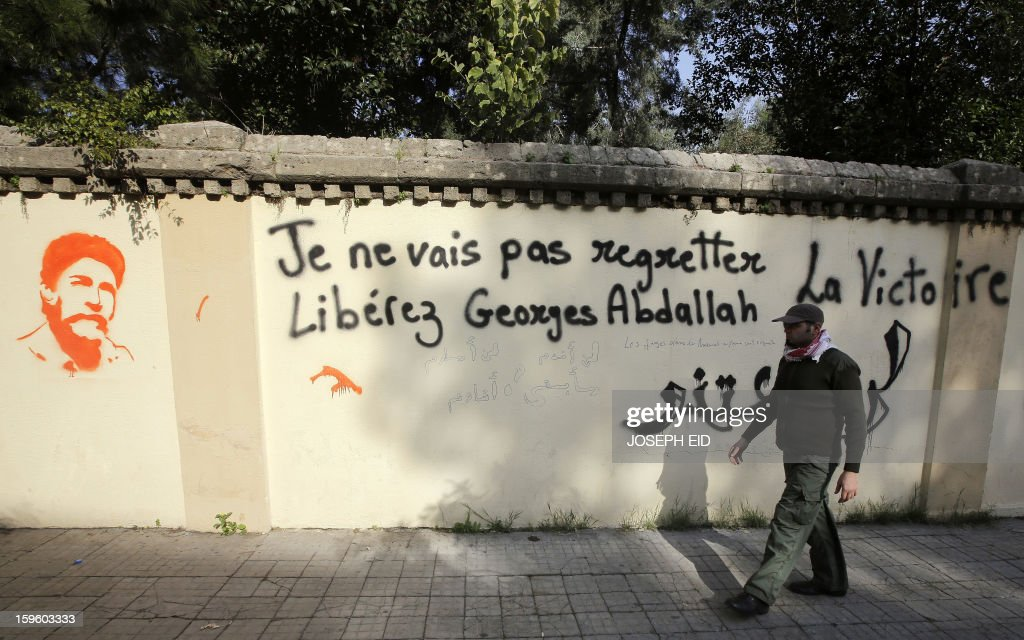 An activist walks past a graffiti of Lebanese militant Georges Ibrahim Abdallah sprayed on a wall opposite to the French embassy in Beirut to protest against the decision by French authorities not to sign the documents for his extradition on January 17, 2013. A French court granted Abdallah, 61, parole in November on condition he be deported but a judicial source said the interior ministry had yet to issue the deportation order. The court postponed its decision on his release until January 28. Abdallah, is imprisoned in France for complicity in the murder of two diplomats in Paris in 1982.