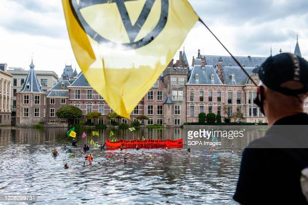 An activist watching a group of XR activists get into the water during the demonstration. The climate activist group, Extinction Rebellion in The...