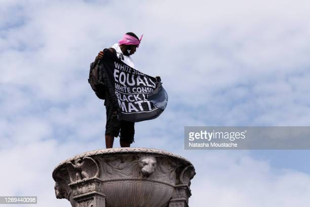 An activist waves a flag in support of Black Lives Matter atop the Lincoln Memorial during the Commitment March on August 28, 2020 in Washington, DC....