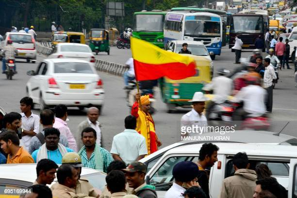 An activist waves a Karnataka state flag during a protest in Bangalore on June 12 2017 ProKannada activists protested to urge government intervention...