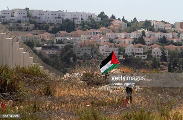 An activist waves Palestinian flag during clashes with Israeli soldiers following a protest against the Jewish settlements and the Israeli Wall of...