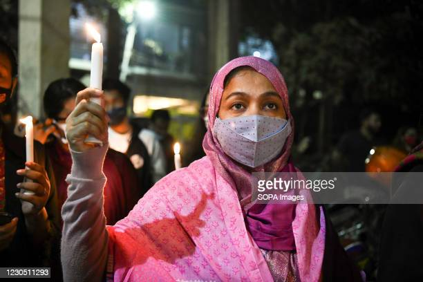 An activist wearing a face mask holds a lit candle during the demonstration. Female activists and classmates take part in a candlelight protest...