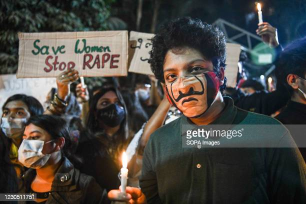 An activist wearing a mask holds a lit candle during the demonstration. Female activists and classmates take part in a candlelight protest demanding...