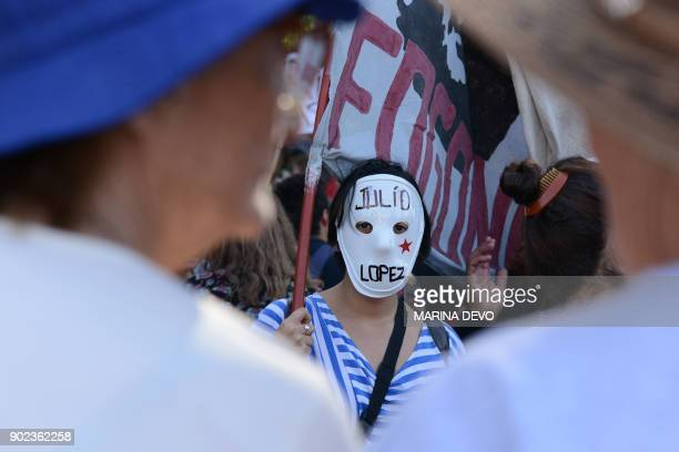 An activist wearing a mask with the name of disappeared Dirty War key witness Julio Lopez demonstrates outside former Buenos Aires police chief...