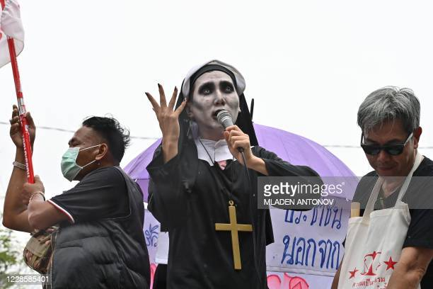 An activist wearing makeup and dressed up as a Catholic nun addresses the crowd from an improvised stage as antigovernment protesters gather for a...