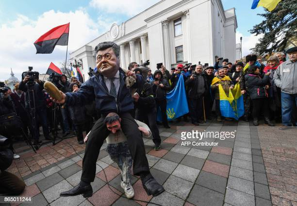 An activist wears a mask depicting Ukraine's President during an opposition rally in front of the Ukrainian parliament in Kiev on October 22 2017...
