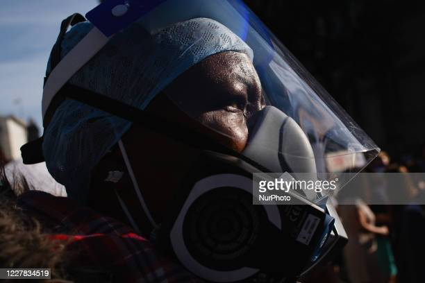 An activist wears a respirator mask and face shield as National Health Service staff, protesting their exclusion from a recently-announced public...