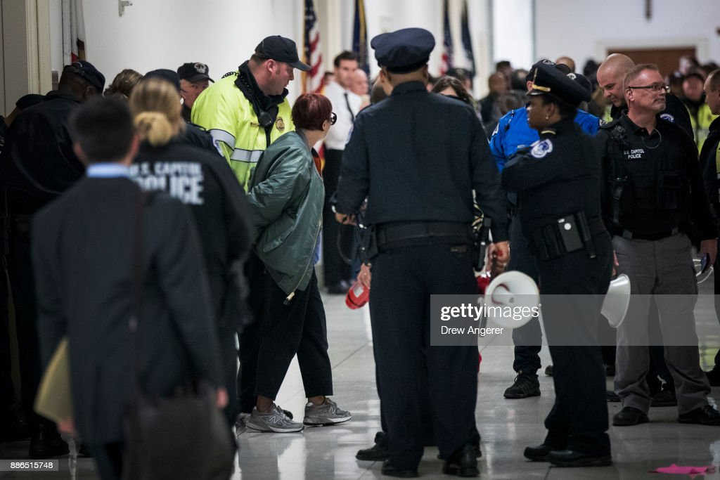 An activist who was protesting agains the GOP tax reform bill is arrested by Capitol Police officers, outside the office of Rep. Dana Rohrabacher (R-CA) on Capitol Hill, December 5, 2017 in Washington, DC. The next step in the legislative process for the GOP tax reform plan is to merge the Senate and House versions in a conference committee.