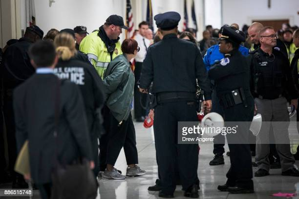 An activist who was protesting agains the GOP tax reform bill is arrested by Capitol Police officers outside the office of Rep Dana Rohrabacher on...