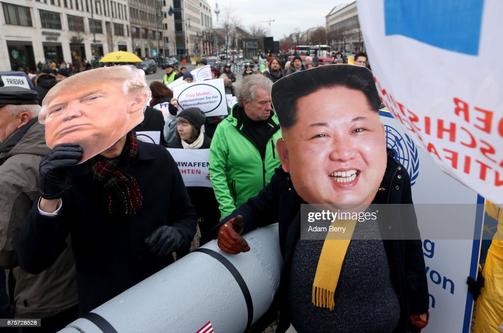 An activist with a mask of Kim Jong-un, chairman of the Workers' Party of Korea and supreme leader of North Korea (R) and another with a mask of U.S. President Donald Trump march with a model of a nuclear rocket during a demonstration against nuclear weapons on November 18, 2017 in Berlin, Germany. About 700 demonstrators protested against the current escalation of threat of nuclear attack between the United States of America and North Korea. The event was organized by peace advocacy organizations including the International Campaign to Abolish Nuclear Weapons (ICAN), which won the Nobel Prize for Peace this year.