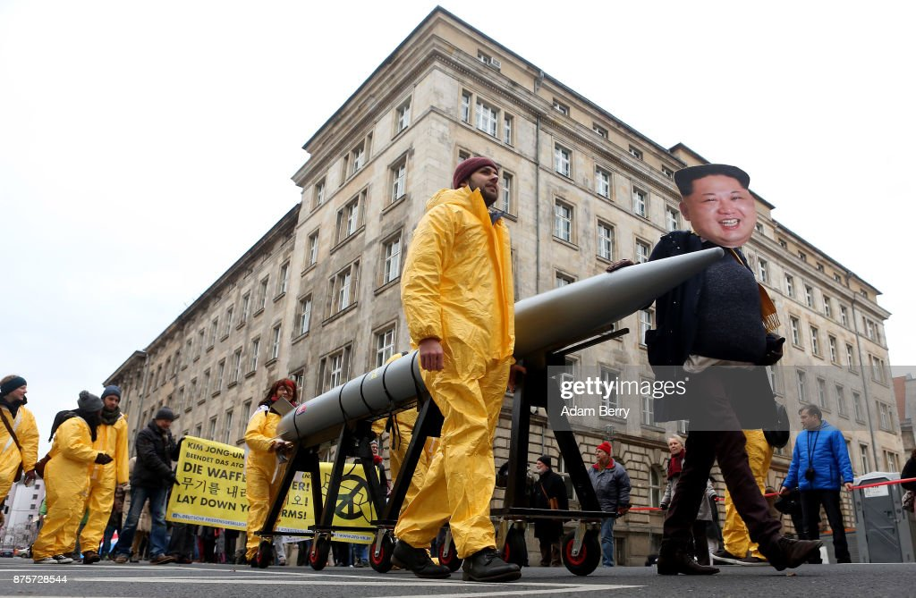An activist with a mask of Kim Jong-un, chairman of the Workers' Party of Korea and supreme leader of North Korea, marches with a model of a nuclear rocket during a demonstration against nuclear weapons on November 18, 2017 in Berlin, Germany. About 700 demonstrators protested against the current escalation of threat of nuclear attack between the United States of America and North Korea. The event was organized by peace advocacy organizations including the International Campaign to Abolish Nuclear Weapons (ICAN), which won the Nobel Prize for Peace this year.