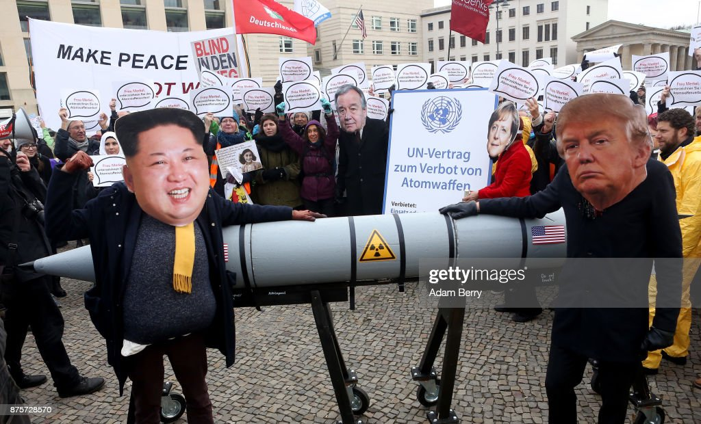An activist with a mask of Kim Jong-un, chairman of the Workers' Party of Korea and supreme leader of North Korea (L), and another with a mask of U.S. President Donald Trump, march with a model of a nuclear rocket during a demonstration against nuclear weapons on November 18, 2017 in Berlin, Germany. About 700 demonstrators protested against the current escalation of threat of nuclear attack between the United States of America and North Korea. The event was organized by peace advocacy organizations including the International Campaign to Abolish Nuclear Weapons (ICAN), which won the Nobel Prize for Peace this year.