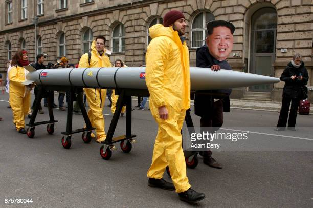 An activist with a mask of Kim Jongun chairman of the Workers' Party of Korea and supreme leader of North Korea marches with a model of a nuclear...