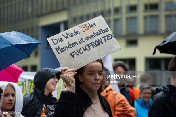 An activist with a sign quoting the German constitution and saying quotFuck Frontexquot in Munich Germany on August 25 2018 Some thousands persons...